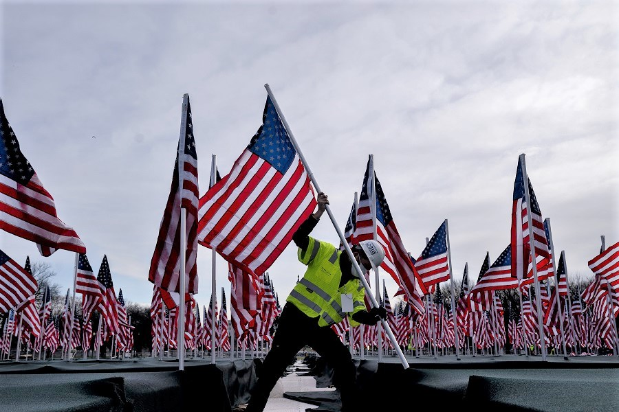 A worker plants an American flag along the National Mall in Washington, DC, US, on 18 January 2021. (Stefani Reynolds/Bloomberg)