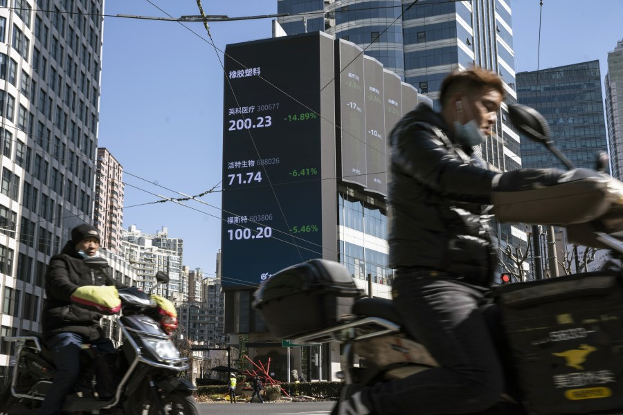 Motorists travel past a screen displaying stock figures in Shanghai, China, on 18 February 2021. (Qilai Shen/Bloomberg)