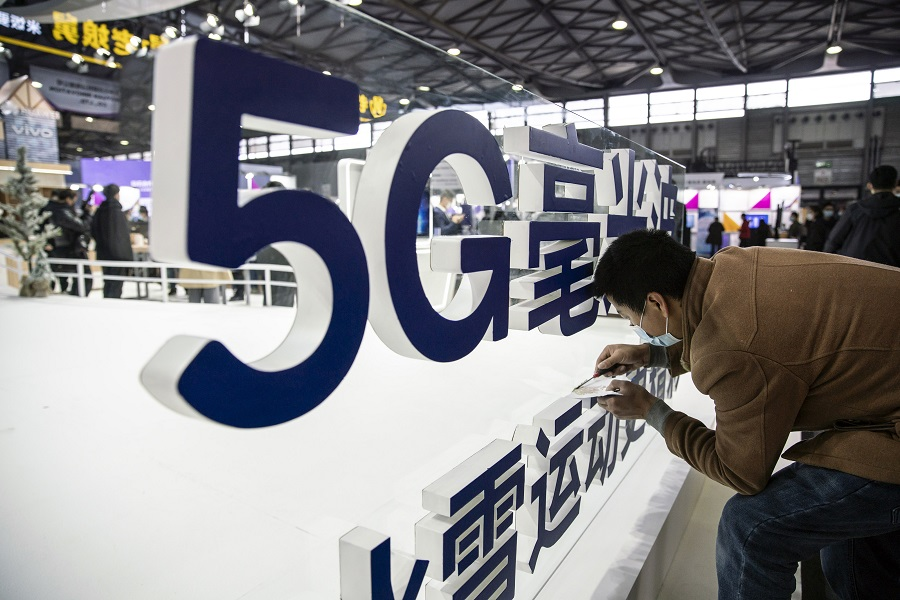 A worker makes finishing touches to a signage for 5G mmWave at the MWC Shanghai exhibition in Shanghai, China, on 23 February 2021. (Qilai Shen/Bloomberg)