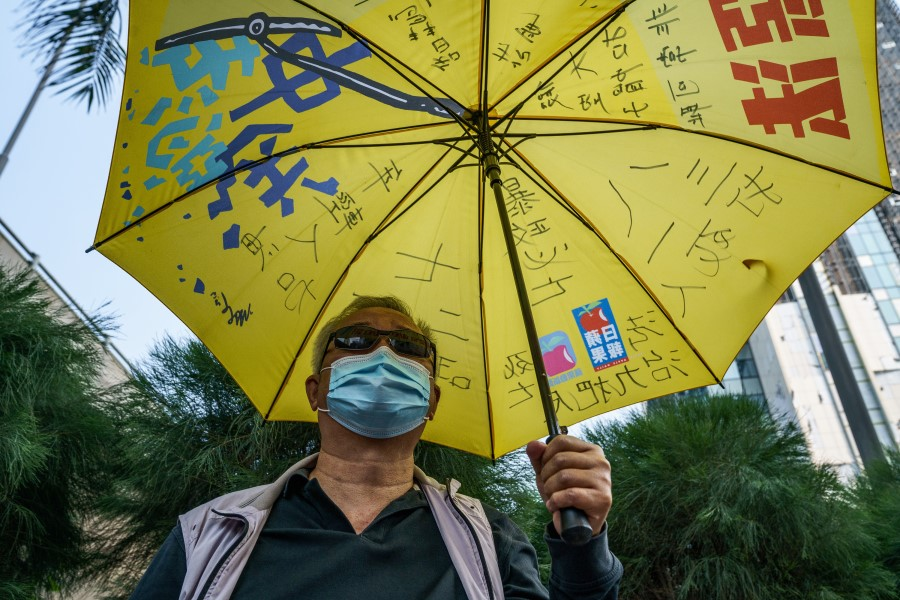 A pro-democracy demonstrator holds a yellow umbrella outside the West Kowloon Magistrates' Courts during a hearing for 47 opposition activists charged with violating the city's national security law in Hong Kong, China, 2 March 2021. (Lam Yik/Bloomberg)