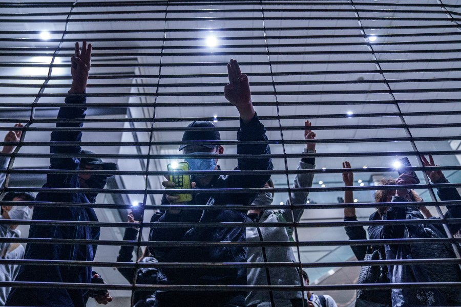 Pro-democracy demonstrators gesture with three-fingered salutes outside West Kowloon Magistrates Courts during a hearing for 47 opposition activists charged with violating the city's national security law in Hong Kong on 4 March 2021. (Lam Yik/Bloomberg)