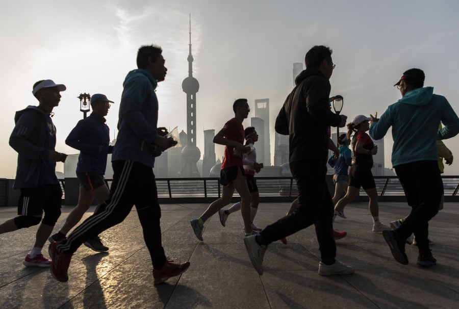 Joggers run along the Bund as the Lujiazui Financial District stands in the background in Shanghai, China, 10 April 2021. (Qilai Shen/Bloomberg)