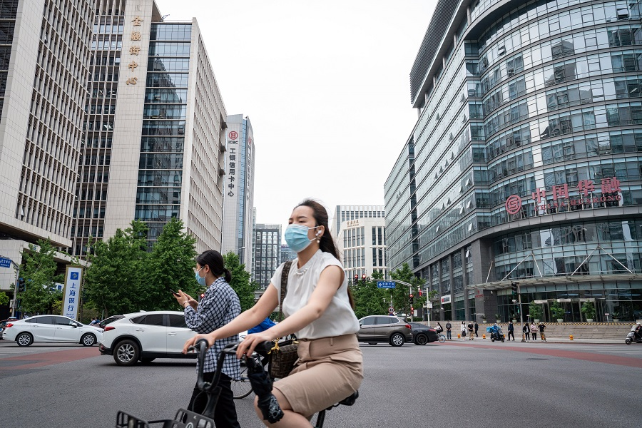 A cyclist and pedestrians wearing protective masks travel past buildings on Financial Street in Beijing, China on 19 May 2021. (Yan Cong/Bloomberg)