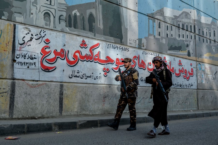 Taliban fighters patrol along a road on the backdrop of a mural painted on the wall of a flyover in Kabul on 26 September 2021. (Hoshang Hashimi/AFP)