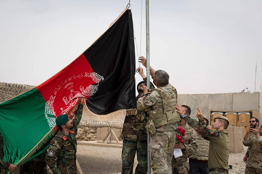 This handout photograph taken on 2 May 2021 and released by Afghanistan's Ministry of Defense shows US soldiers and Afghan National Army soldiers raising Afghanistan's national flag during a handover ceremony to the Afghan National Army army 215 Maiwand corps at Antonik camp in Helmand province, Afghanistan. (Afghanistan Ministry of Defense/AFP)