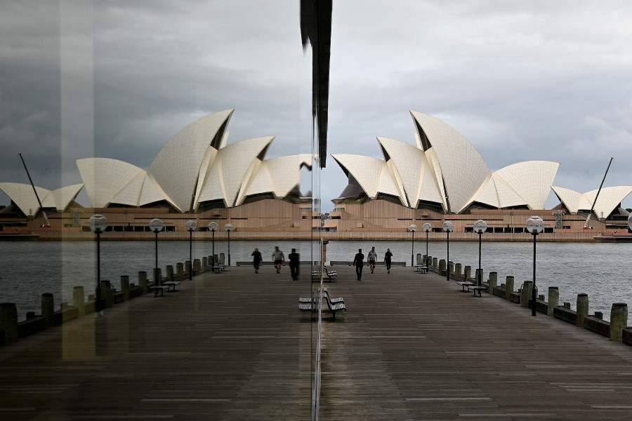 People walk before the Opera House, usually packed with tourists, in Sydney, on 18 May 2020. (Saeed Khan/AFP)