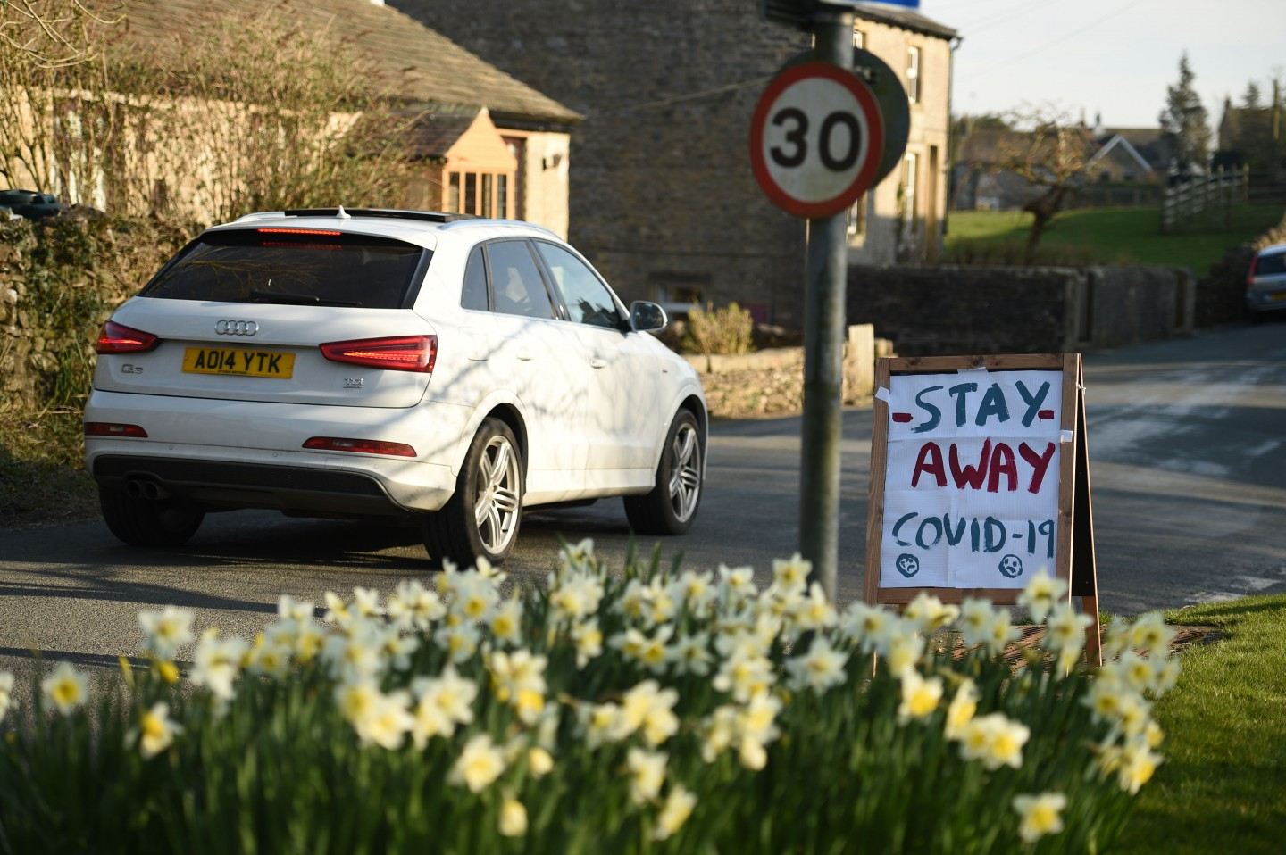 """A sign instructing tourists to """"Stay Away"""" is seen beside the road in the village of Airton in northern England on 22 March 2020. (Oli Scarff/AFP)"""