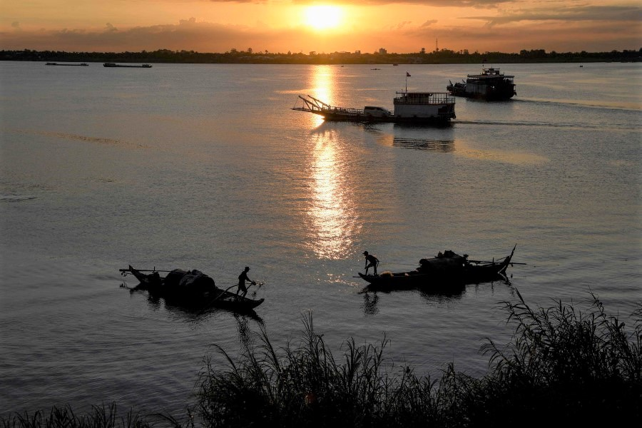 Fishermen pull in their fishing nets as the sun rises over the Mekong river in Phnom Penh on 9 June 2020. (Tang Chhin Sothy/AFP)