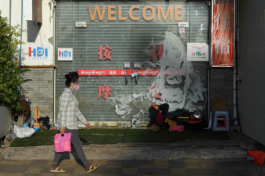 A woman walks past a closed shop in Phnom Penh, Cambodia, on 25 June 2021. (Tang Chhin Sothy/AFP)
