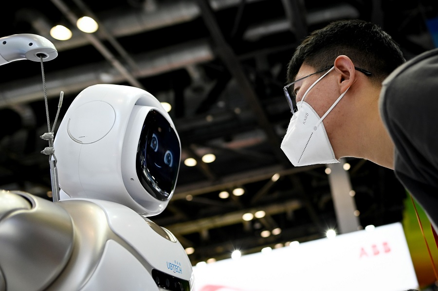 A man wearing a face mask looks at a robot at the China National Convention Centre, the venue for the upcoming the China International Fair for Trade in Services (CIFTIS) in Beijing on 3 September 2020. (Wang Zhao/AFP)