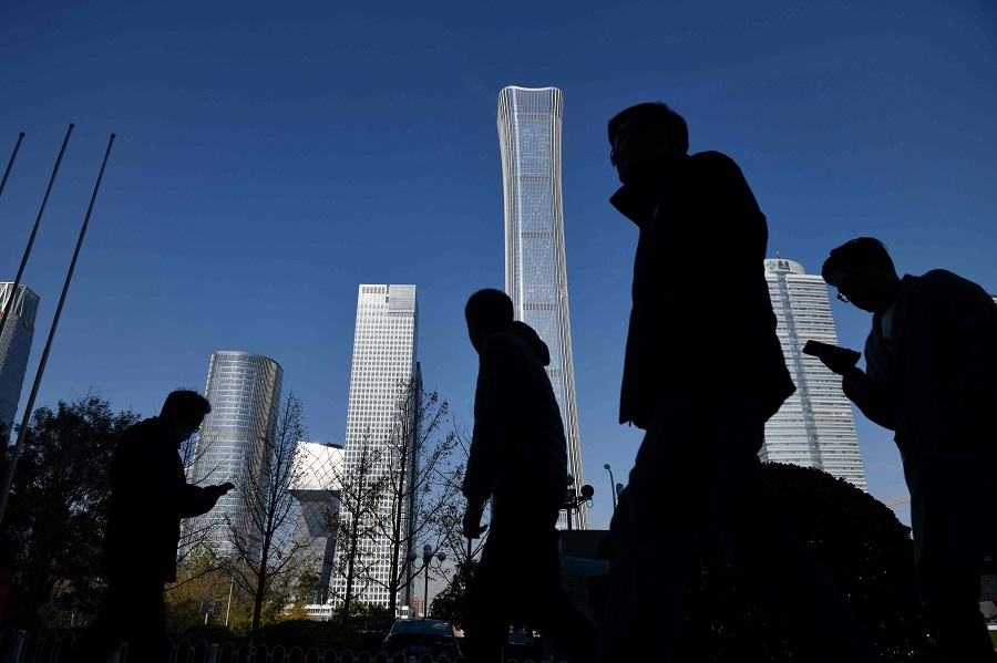 People walk past skyscrapers in the central business district in Beijing, China, on 24 November 2020. (Greg Baker/AFP)