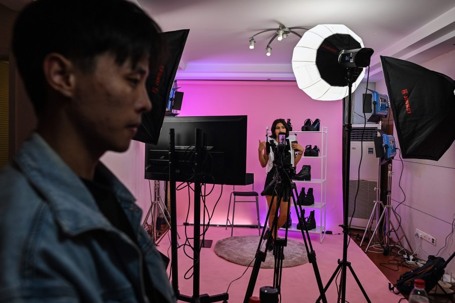 This photo taken early on October 23, 2020 shows Silvia Rivera (in background) attending a live-streaming event from a studio in Shanghai to offer products on an Aliexpress channel in Spain. By some estimates,livestreamshopping is a near US$70 billion industry insideChina. (Hector Retamal/AFP)