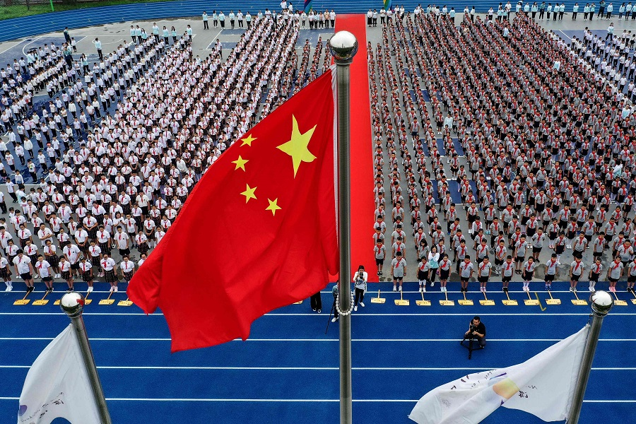 This aerial photo taken on 1 September 2020 shows elementary school students attending a flag-raising ceremony on the first day of the new semester in Shenyang, Liaoning, China. (STR/AFP)