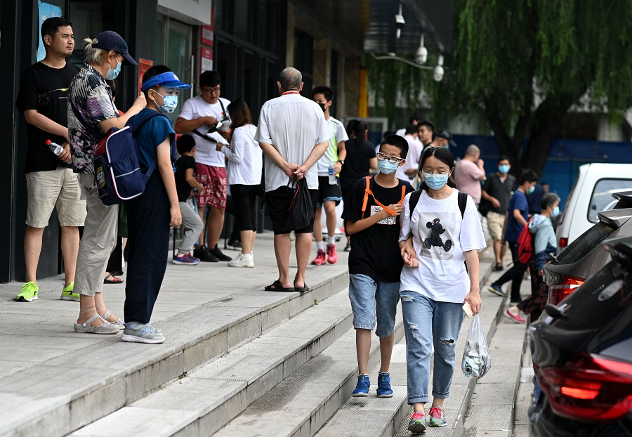 This picture taken on 28 July 2021 shows students walking with their guardians after attending private after-school education in Haidan district of Beijing, China. (Noel Celis/AFP)