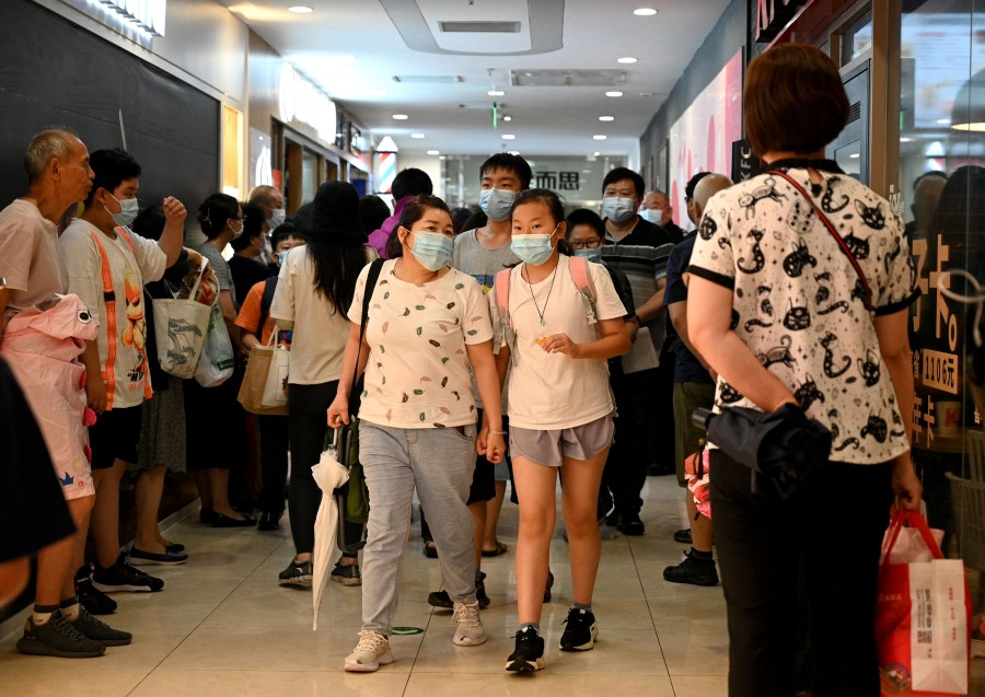 This picture taken on 29 July 2021 shows students and parents walking after attending a private after-school education in Haidan district of Beijing. (Noel Celis/AFP)