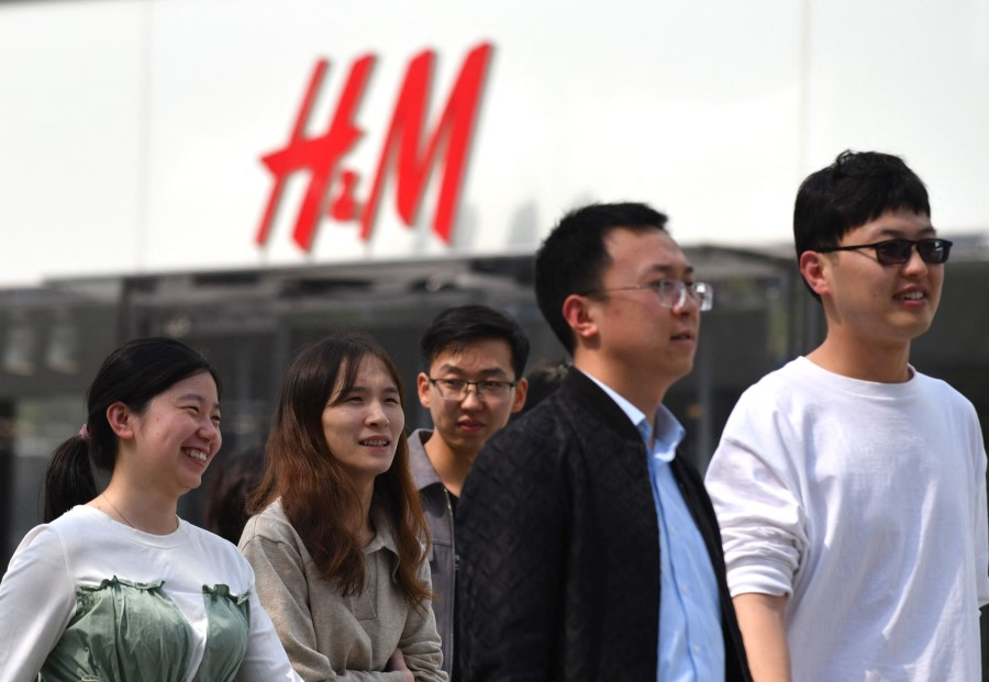 People walk past an H&M clothing store in Beijing on 25 March 2021. (Greg Baker/AFP)