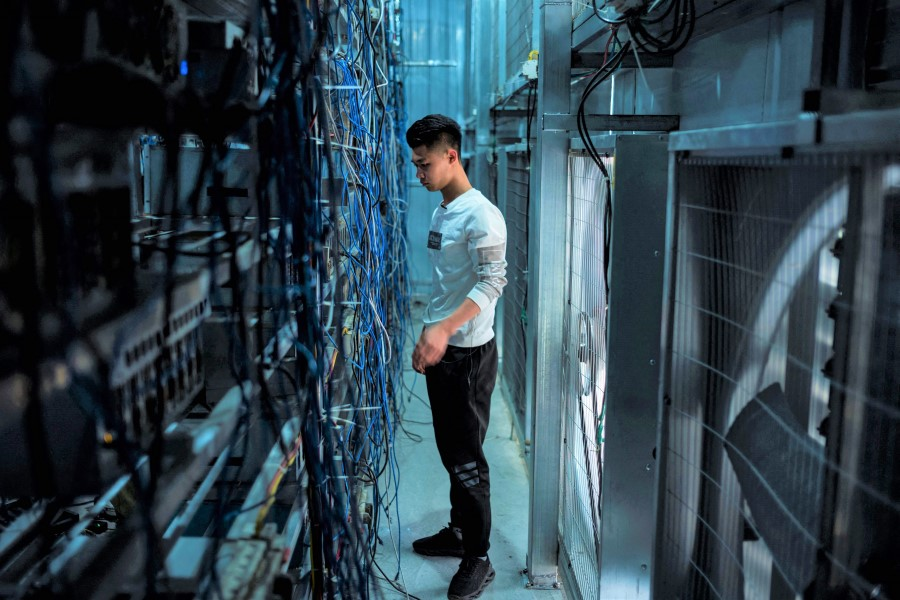 This photo taken on 1 April 2021 shows a worker adjusting cryptocurrency mining rigs at a cryptocurrency farm in Dujiangyan in China's southwestern Sichuan province. (STR/AFP)