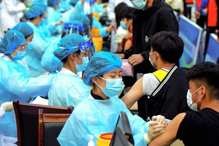 This photo taken on 30 March 2021 shows a medical staff member (centre) administering a dose of the Sinovac Covid-19 coronavirus vaccine at a university in Qingdao in China's eastern Shandong province. (STR/AFP)