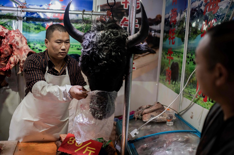 This picture taken on 15 January 2020 shows a butcher selling a yak's head to a customer at a market in Beijing. (Nicolas Asfouri/AFP)