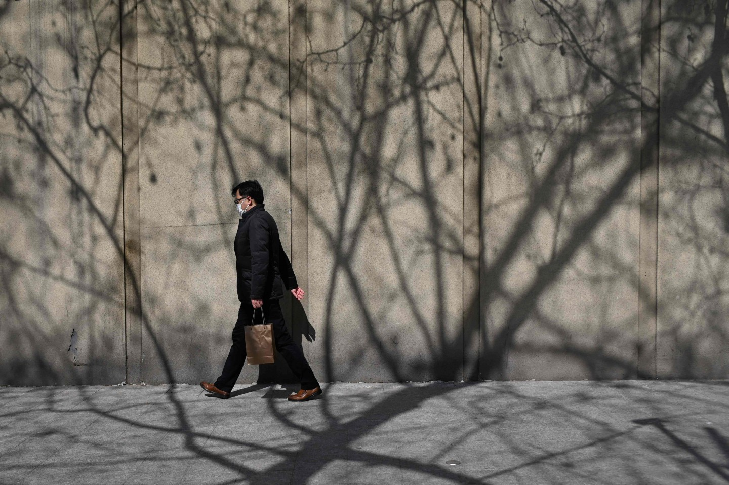 A man wearing a face mask walks along a road in Beijing on 11 March 2020. (Wang Zhao/AFP)