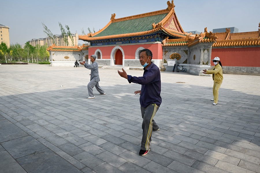 This picture taken on 30 April 2020 shows people wearing face masks, amid concerns of the Covid-19 coronavirus, practising Tai Chi at a park in Beijing. (Wang Zhao/AFP)