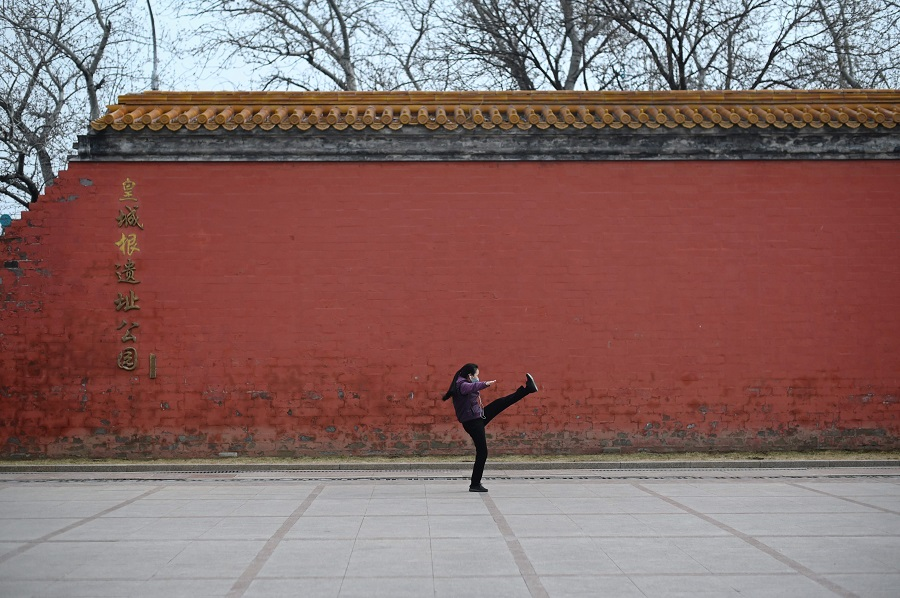 This picture taken on 21 February 2020 shows a woman wearing a face mask, amid concerns of the Covid-19 coronavirus, exercising at a park in Beijing. (Wang Zhao/AFP)
