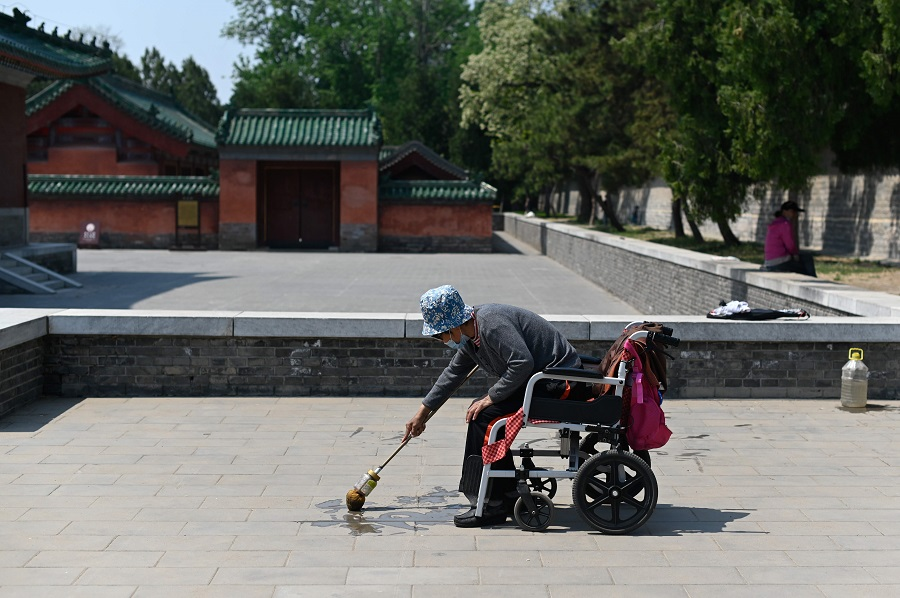 An elderly woman wearing a face mask practises water calligraphy on a pavement in Beijing on 27 April 2020. (Wang Zhao/AFP)
