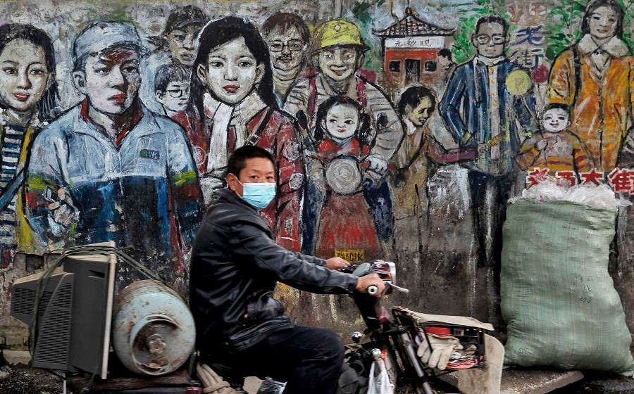 A man wearing a face mask amid the Covid-19 pandemic drives his motorbike along a street in Wuhan, China, on 24 April 2020. (STR/AFP)