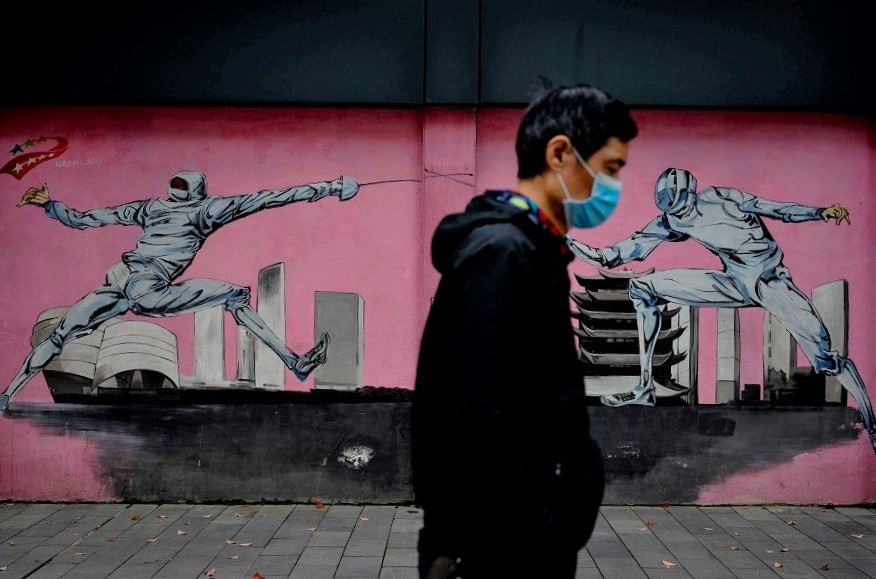 A man wearing a face mask walks past a mural along a street in Wuhan, China, on 2 April 2020. (Noel Celis/AFP)