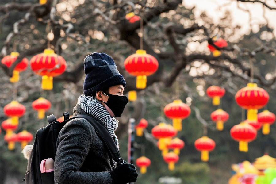 A man wears a protective face mask amid the Covid-19 pandemic, as he walks past the Jingshan park overlooking the Forbidden City in Beijing on 25 January 2020. (Nicolas Asfouri/AFP)