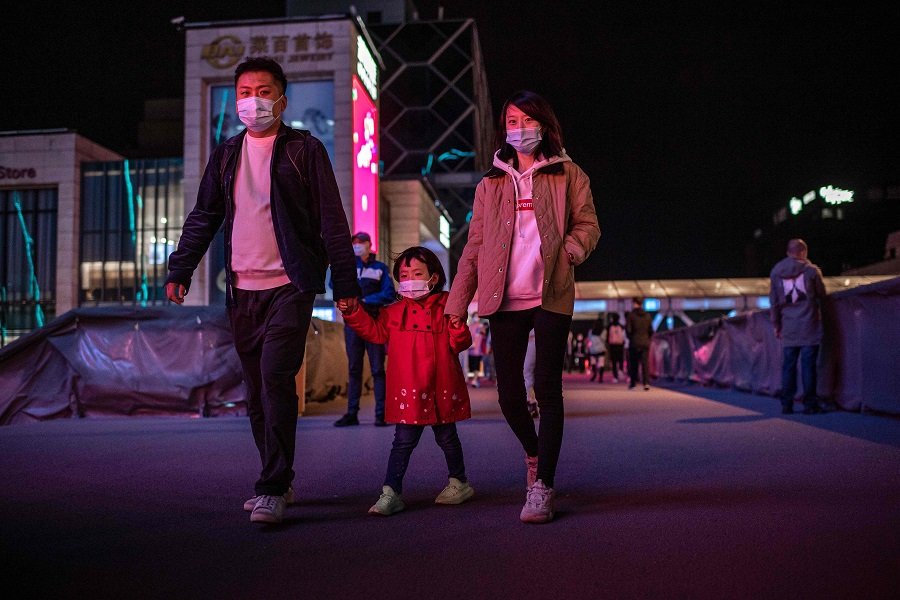A family wearing face masks walks outside a shopping mall in Beijing on 11 October 2020. (Nicolas Asfouri/AFP)