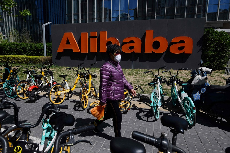 A woman walks past an Alibaba sign outside the company's office in Beijing, China, on 13 April 2021. (Greg Baker/AFP)