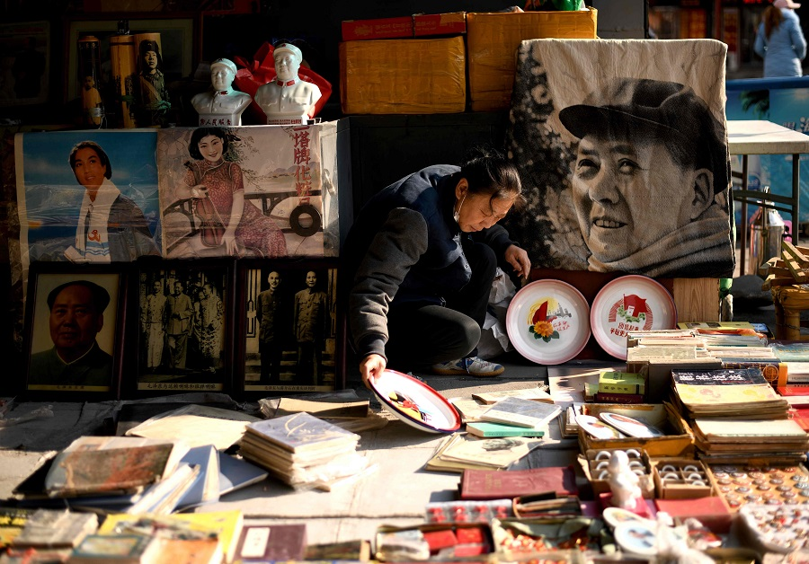 A vendor arranges books at her stall at the Panjiayuan antique market in Beijing, China, on 19 November 2020. (Noel Celis/AFP)