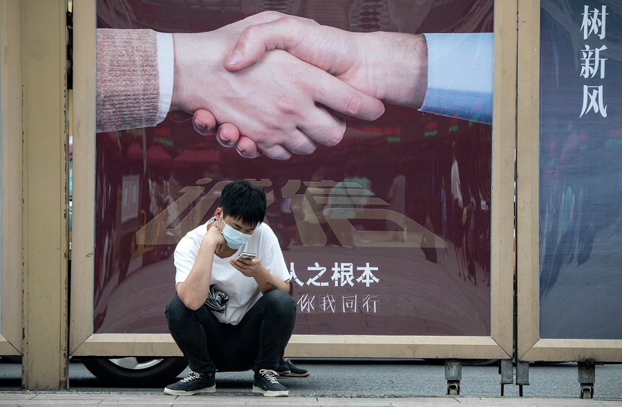 A man uses his phone outside Beijing Railway Station in Beijing on 19 August 2020. (Noel Celis/AFP)