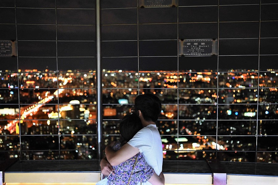 A couple hug as they look out at a night view through a fence at the Central Television Tower in Beijing, China, on 26 August 2021. (Jade Gao/AFP)