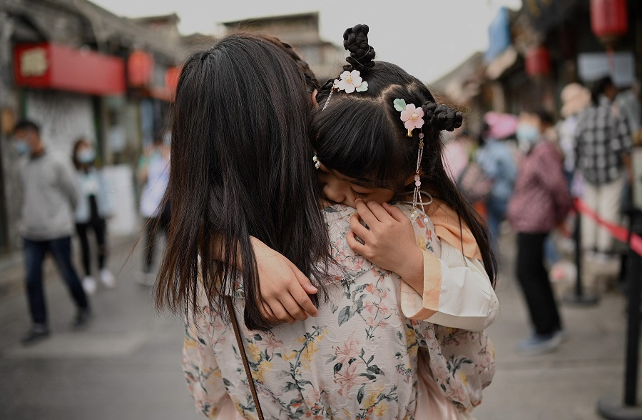 A mother carrying her child in an alley near Houhai Lake in Beijing, China on 4 May 2021. (Noel Celis/AFP)