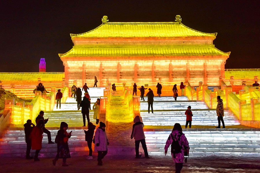 This photo taken on 11 December 2020 shows tourists looking at an illuminated ice sculpture at the Changchun ice and snow grand world in Changchun, Jilin province, China. (STR/AFP)