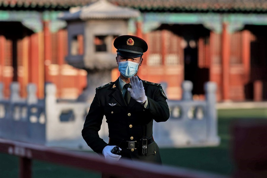 A soldier wearing a face mask gestures outside the Forbidden City in Beijing on 22 October 2020. (Nicolas Asfouri/AFP)