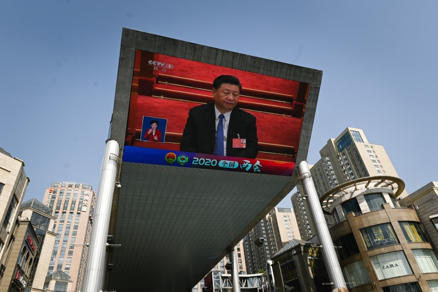 An outdoor screen shows live coverage of China's President Xi Jinping attending the closing session of the National People's Congress (NPC) in Beijing, 28 May 2020. (Wang Zhao/AFP)