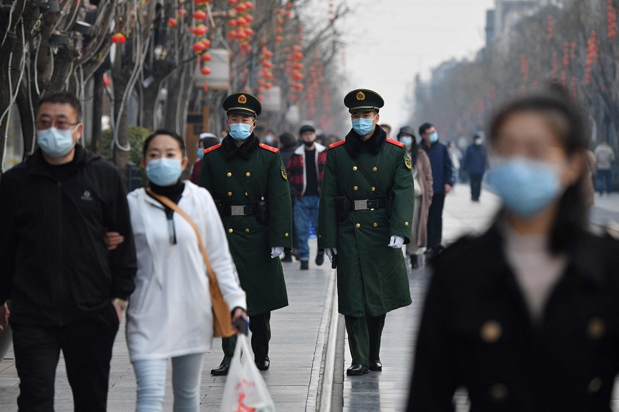 Two paramilitary police officers patrol in the area south of the Great Hall of the People during the second plenary session of the National People's Congress in Beijing on 8 March 2021. (Greg Baker/AFP)