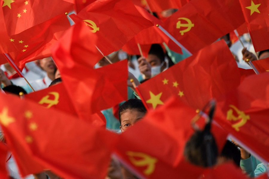 Students wave flags of China and the Communist Party of China before celebrations in Beijing, China, on 1 July 2021, to mark the 100th anniversary of the founding of the Communist Party of China. (Wang Zhao/AFP)