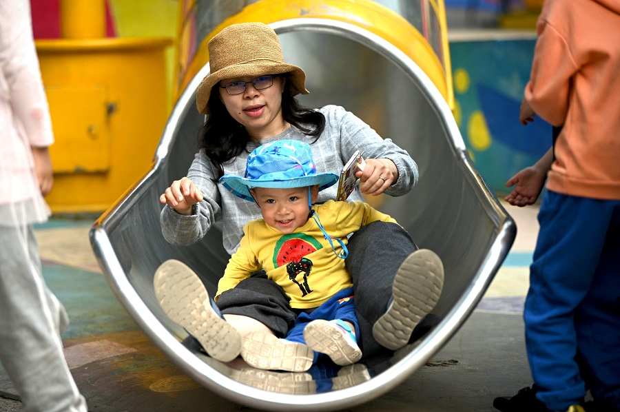 A mother and her baby play on a slide at Wukesong shopping district in Beijing, China on 11 May 2021. (Noel Celis/AFP)