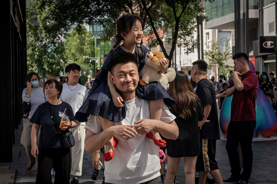 A young girl sits on her father's shoulders outside a shopping mall in Beijing, China, on 1 June 2021. (Nicolas Asfouri/AFP)
