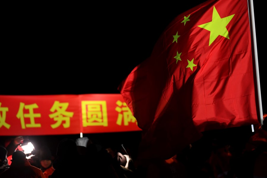 A Chinese flag is seen at the landing site of the return module of China's Chang'e-5 lunar probe in Siziwang Banner, in northern China's Inner Mongolia Autonomous Region on 17 December 2020. (STR/AFP)