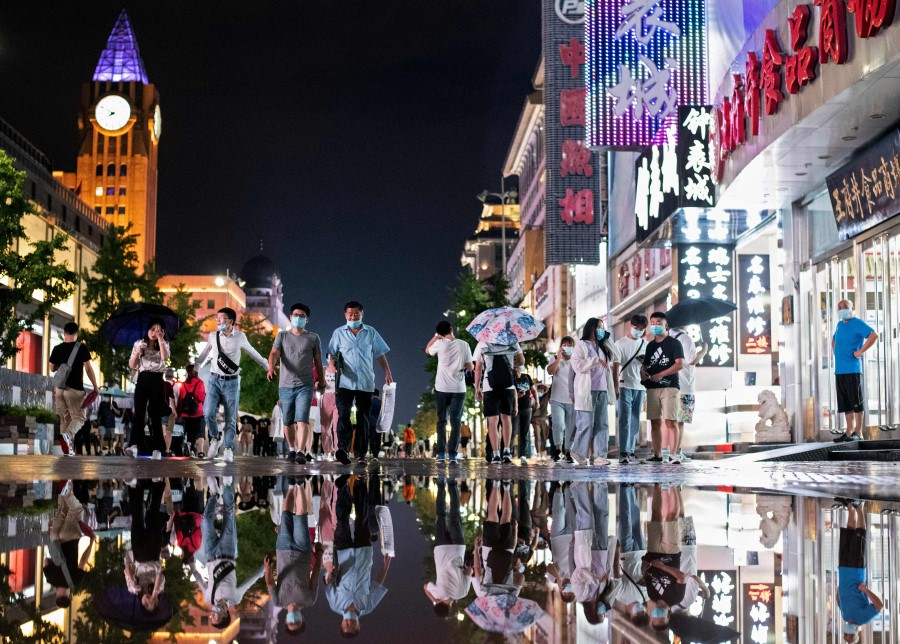People are reflected in a puddle after a rainfall as they walk along a shopping district in Beijing on 18 August 2020. (Noel Celis/AFP)