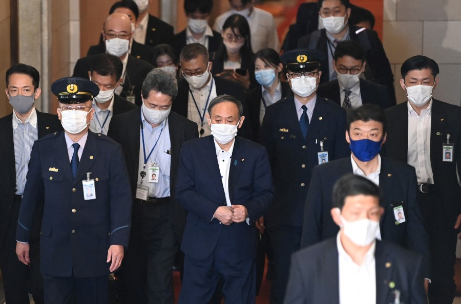 Japan's Prime Minister Yoshihide Suga (centre) leaves after a lower house budget committee session at parliament in Tokyo on 10 May  2021. (Kazuhiro Nogi/AFP)