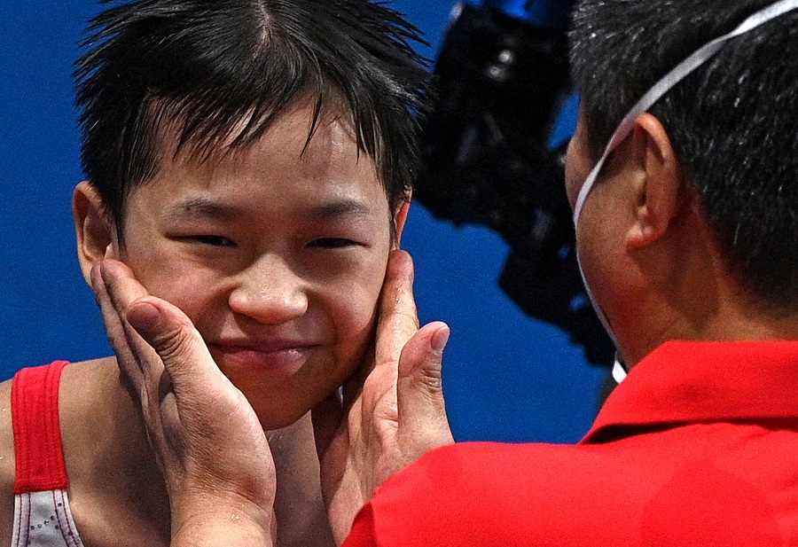 China's Quan Hongchan is congratulated by a coach after winning the women's 10m platform diving finals event during the Tokyo 2020 Olympic Games at the Tokyo Aquatics Centre in Tokyo, Japan on 5 August 2021. (Oli Scarff/AFP)
