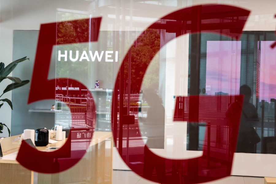 """A shop for Chinese telecom giant Huawei features a red sticker reading """"5G"""" in Beijing, 25 May 2020. (Nicolas Asfouri/AFP)"""