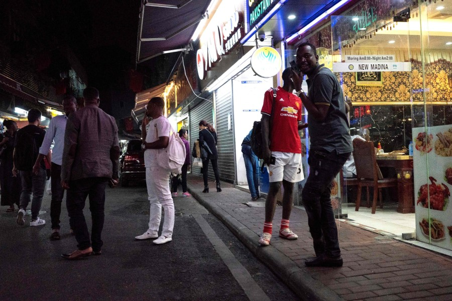 """This file photo taken on March 2, 2018 shows people gathering on a street in the """"Little Africa"""" district in Guangzhou, the capital of southern China's Guangdong province. Africans in southern China's largest city say they have become targets of suspicion and subjected to forced evictions, arbitrary quarantines and mass coronavirus testing. (Fred Dufour/AFP)"""