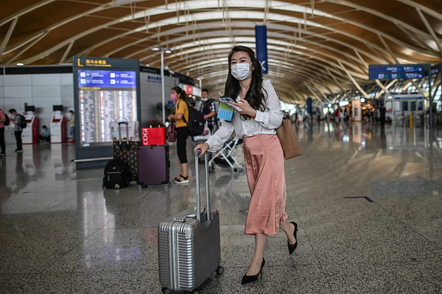 In this file photo, passengers wearing face masks are seen in Pudong International Airport in Shanghai on 11 June 2020. (Hector Retamal/AFP)
